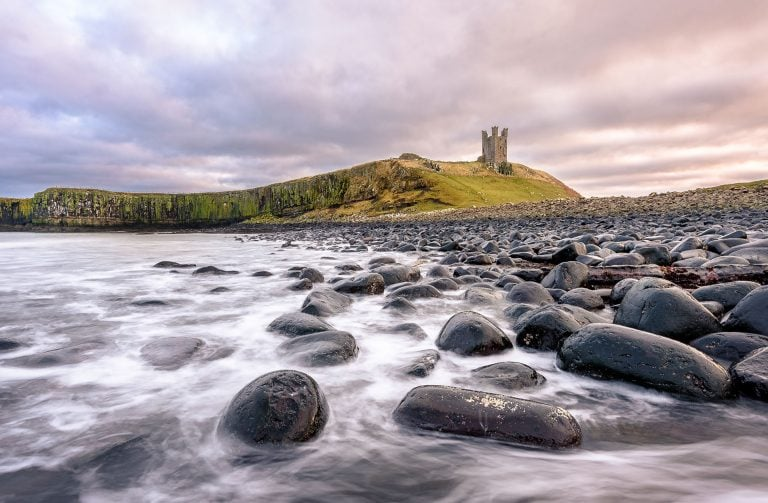 landscape sunset photo of dunstanburgh castle in northumberland
