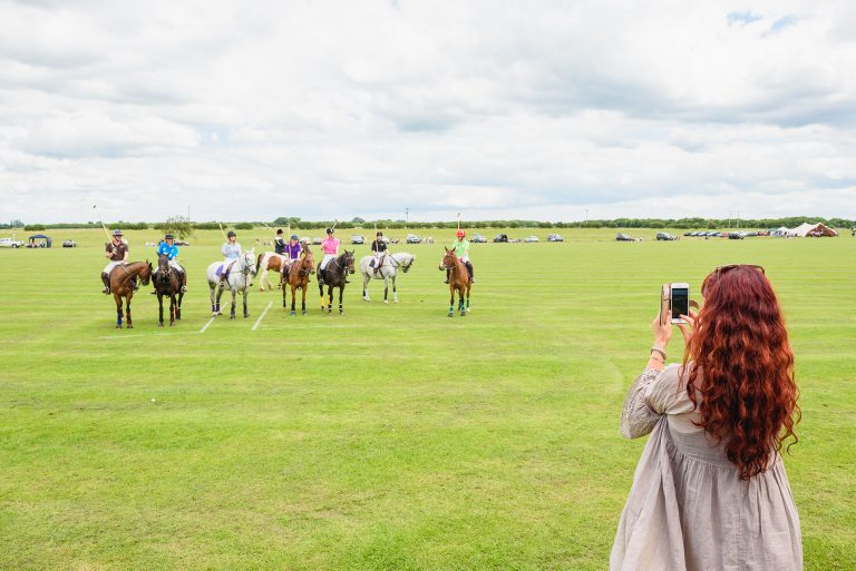 photo of a girl taking pictures of horses